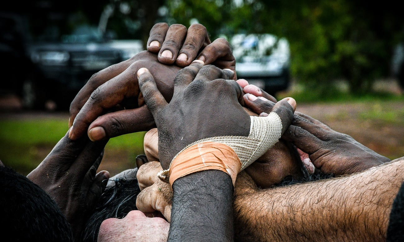 The Tiwi Bombers players join hands during their clash with the Crocs: Photo Jack Banister