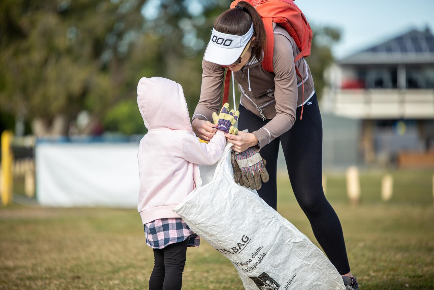 Volunteer mum placing gloves on young daughter